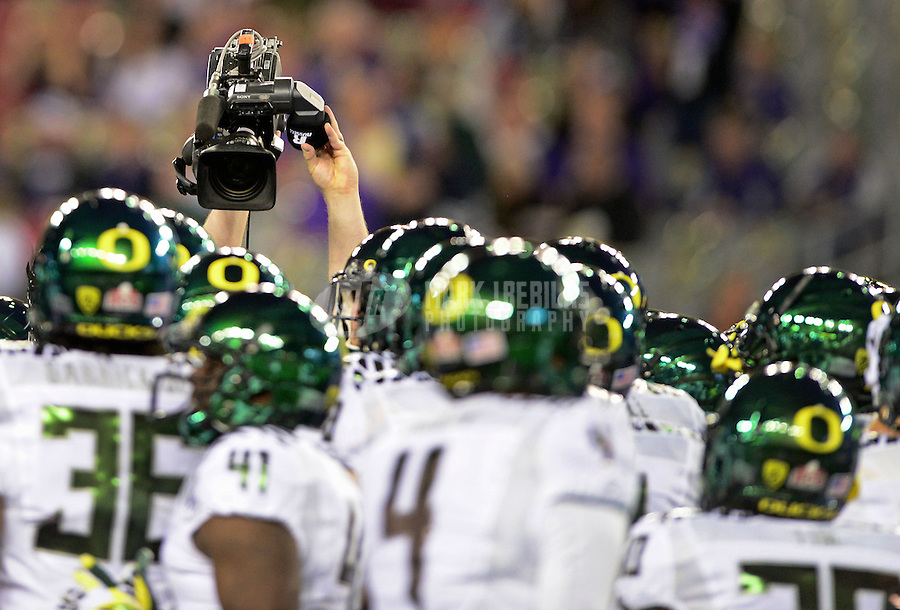 Jan. 3, 2013; Glendale, AZ, USA: A television camera is held above Oregon Ducks players as they huddle on the field prior to the game against the Kansas State Wildcats during the 2013 Fiesta Bowl at University of Phoenix Stadium. Oregon defeated Kansas State 35-17. Mandatory Credit: Mark J. Rebilas-