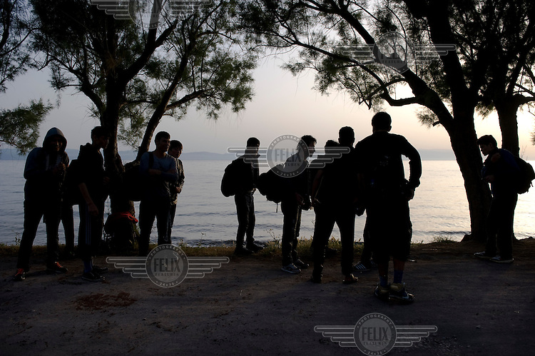 A group of Afghan refugees are gathered on the beach of Skala Sykaminias. Every day hundreds of refugees, mainly from Syria and Afghanistan, are crossing in small overcrowded inflatable boats the 6 mile channel from the Turkish coast to the island of Lesbos in Greece. Many spend their life savings, over $1,000, to buy a space on these boats.