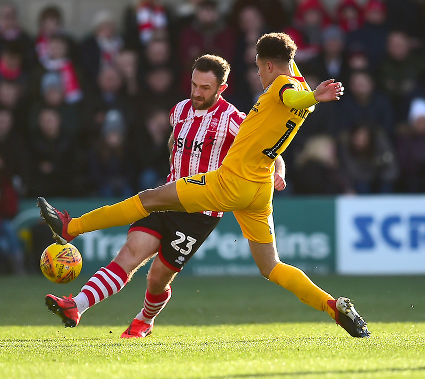 Lincoln City's Neal Eardley clears under pressure from Northampton Town's Shaun McWilliams<br /> <br /> Photographer Andrew Vaughan/CameraSport<br /> <br /> The EFL Sky Bet League Two - Lincoln City v Northampton Town - Saturday 9th February 2019 - Sincil Bank - Lincoln<br /> <br /> World Copyright © 2019 CameraSport. All rights reserved. 43 Linden Ave. Countesthorpe. Leicester. England. LE8 5PG - Tel: +44 (0) 116 277 4147 - admin@camerasport.com - www.camerasport.com