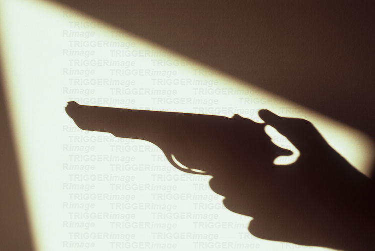 Shadow of hand holding gun or pistol with thumb cocked framed in warm light of shadow from window or door