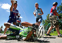 Vong Philavanh of Fort Collins, Col. is sprayed with a water bottle by Jack Piper of Iowa City after Philavanh fell to the pavement in exaustion near the top of a mile long hill ascending from the Des Moines River valley west of Boone on RAGBRAI XXXVI.
