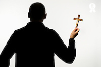 Silhouette of man holding crucifix (Licence this image exclusively with Getty: http://www.gettyimages.com/detail/sb10068346bh-001 )