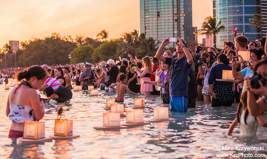 Spectators photographing lanterns floating in the water during the 15th Annual Lantern Floating Ceremony at Ala Moana Beach Park in Honolulu on Memorial Day