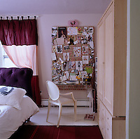 A Perspex desk sits in the corner in front of a large pinboard in this teenage girl's bedroom