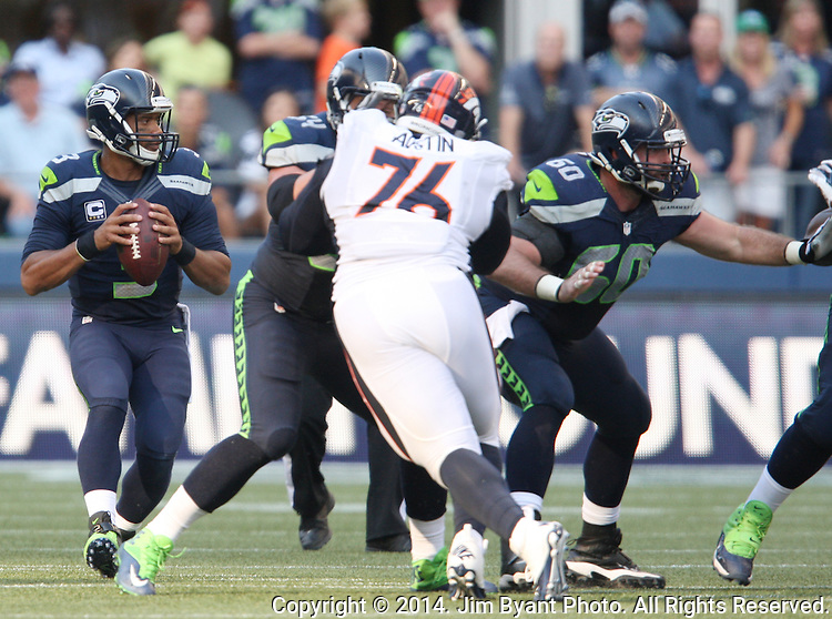 Seattle Seahawks quarter Russell Wilson (3) looks to pass against the Denver Broncos  at CenturyLink Field in Seattle, Washington on September 21, 2014.  Wilson completed 24 of 34 passes for 258 yards, two touchdowns and one interception in the 26-20 overtime win against the Broncos.  ©2014. Jim Bryant Photo. All rights Reserved.