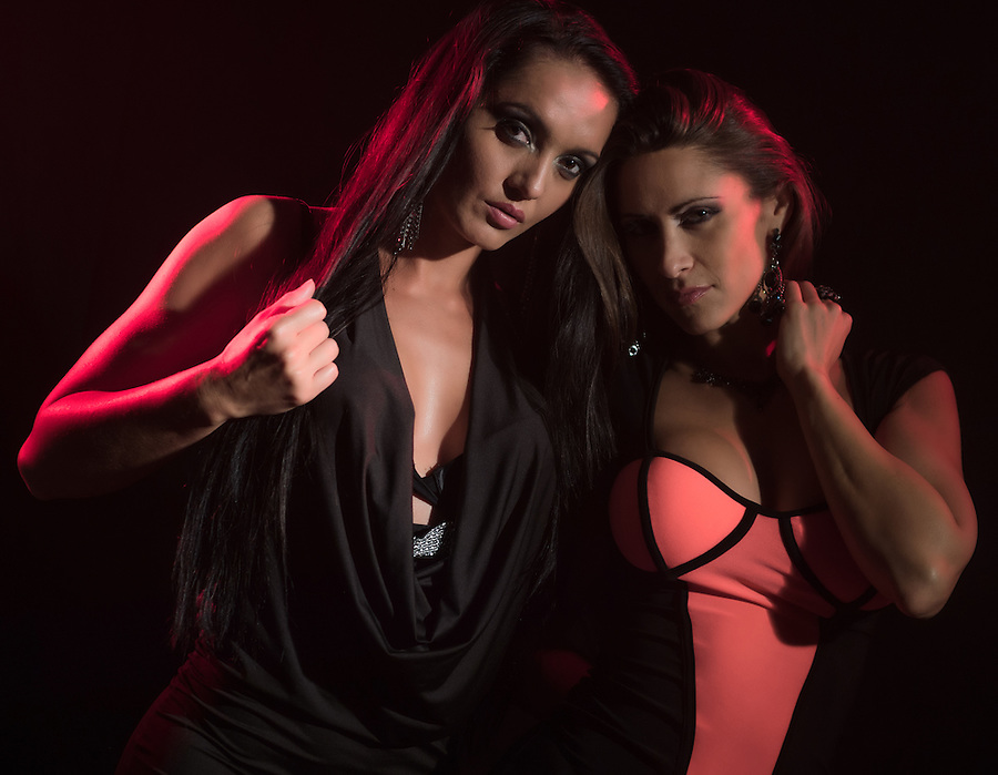 Portrait of 2 sensual woman with night dresses under a red light looking at camera