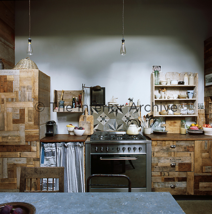 An eclectic kitchen with an imaginative use of reclaimed materials. Squirrel cage light bulbs from Historic Lighting hang by long flexes from the ceiling above the galvanised metal dining table. The splash back is made up of Portuguese tiles bought in Lewes, while cut up crates were used to make cupboard doors.