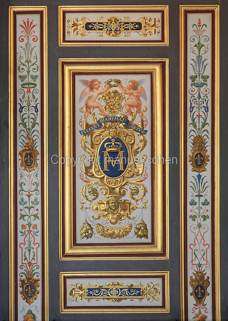 Painted decorative wall panels, with initial M and putti, 19th century, in the Guard Room, Chateau de Fontainebleau, France. The Guard Room is the first of the King's apartment and was occupied by the soldiers of the guard. The Palace of Fontainebleau is one of the largest French royal palaces and was begun in the early 16th century for Francois I. It was listed as a UNESCO World Heritage Site in 1981. Picture by Manuel Cohen