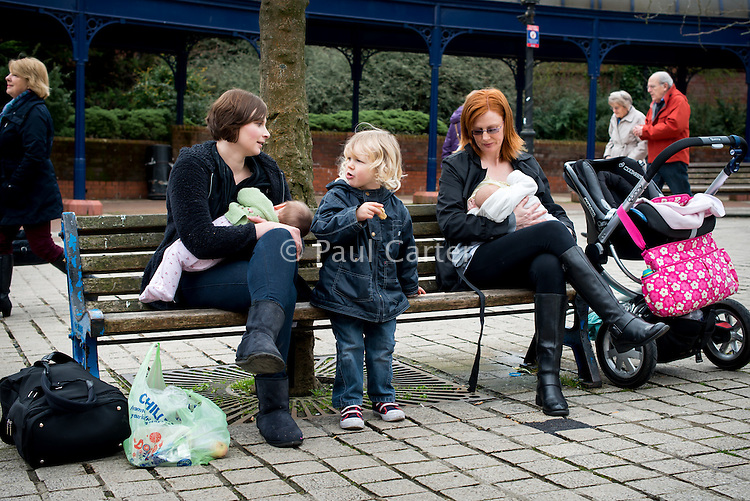 Women chat while sitting on benches in the precinct outside a supermarket breastfeeding their babies. Other shoppers are passing by in the background.<br /> <br /> Image from the &quot;We Do It In Public&quot; documentary photography project collection: <br />  www.breastfeedinginpublic.co.uk<br /> <br /> Dorset, England, UK<br /> 17/04/2013