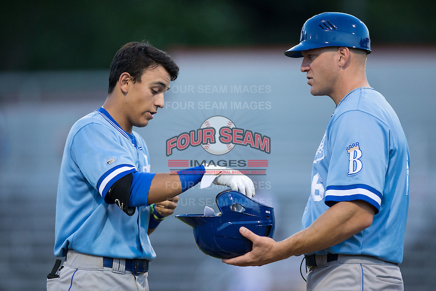 Nicky Lopez (left) hands his gear to Burlington Royals manager Scott Thorman (16) after the third out of an inning during the game against the Danville Braves at American Legion Post 325 Field on August 16, 2016 in Danville, Virginia.  The game was suspended due to a power outage with the Royals leading the Braves 4-1.  (Brian Westerholt/Four Seam Images)
