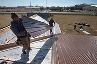 NWA Democrat-Gazette/CHARLIE KAIJO Leo Salazar of Springdale (from left) and Luis Miguel of Springdale lay out metal roofing on Thursday, January 4, 2018 at Outside The Box NWA flea market in Rogers.<br />