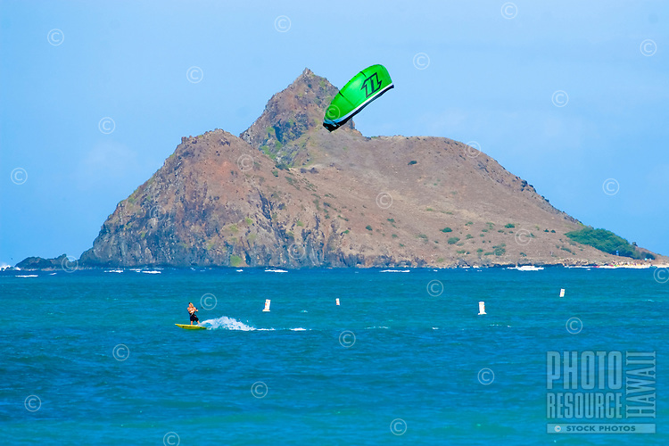 Kitesurfer speeds along with Moku Nui in background