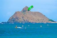 Kitesurfer speeds along with Moku Nui in background