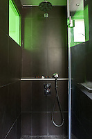 This contemporary shower unit boasts black wall tiles and is illuminated by a window of lime green glass