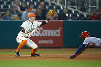 Greensboro Grasshoppers third baseman Patrick Dorrian (15) waits for the throw as Juan Pascal (10) of the Hagerstown Suns slides into third base at First National Bank Field on April 6, 2019 in Greensboro, North Carolina. The Suns defeated the Grasshoppers 6-5. (Brian Westerholt/Four Seam Images)
