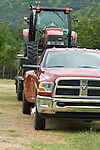 2010 Dodge Ram Crew Cab Dually towing a trailer with a tractor on it