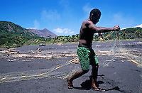 Fisherman on a black sand beach preparing his nets, Sulphur Bay Village, Tanna Island, Vanuatu.