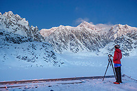 Woman photographer taking photos from deck of Sheldon Chalet on the Ruth Glacier and Amphitheater in the Alaska Range.  Denali / Mt. Mckinley background   <br /> <br /> Photo by Jeff Schultz/SchultzPhoto.com  (C) 2017  ALL RIGHTS RESERVED