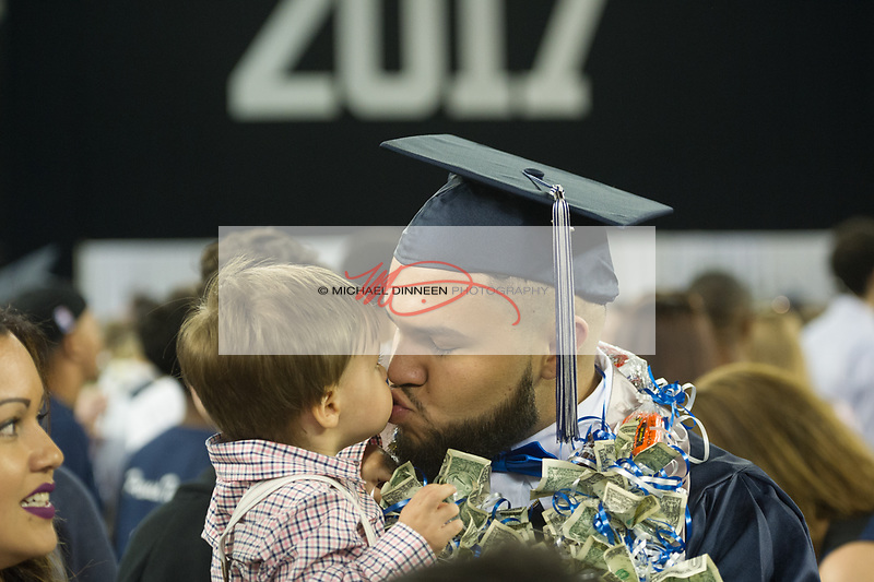 0645<br /> <br /> Eagle River graduate Juan Raymundo kisses his 16-month-old son Mason following the ceremony.  Photo for the Star by Michael Dinneen.