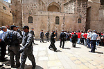 """Israeli soldiers stand guard as Christians Orthodox take part in Easter """"Holy Fire"""" celebrations on the eve of Easter Sunday on April 23, 2011, outside the Church of the Holy Sepulchre, built over the sites where Christians believe Christ was crucified and buried in Israeli annexed east Jerusalem's Old City. Tens of thousands of Christian pilgrims from Eastern churches converged on the Holy City to take part in the Easter """"Holy Fire"""" vigil in which the """"miracle"""" light from Jesus' tomb is shared by candles to the crowd. Photo by Sliman Khader"""