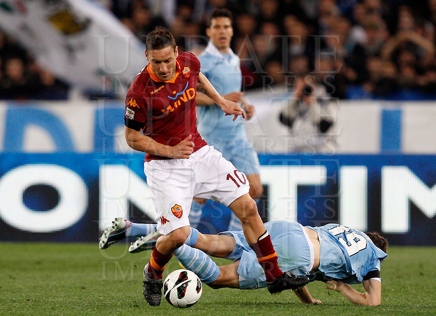 Calcio, Serie A: Roma vs Lazio. Roma, stadio Olimpico, 8 aprile 2013..AS Roma forward Francesco Totti in action past Lazio midfielder Senad Lulic, of Bosnia, bottom, during the Italian Serie A football match between AS Roma and Lazio at Rome's Olympic stadium, 8 April 2013..UPDATE IMAGES PRESS/Riccardo De Luca