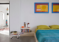 In the bedroom, the bed is set on a built-in, raised tadelakt platform. The bedding is in bold blue and lime green and a pair of colourful prints on the wall complete the picture.