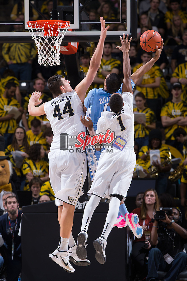Nate Britt (0) of the North Carolina Tar Heels drives to the basket between Dinos Mitoglou (44) and Madison Jones (1) of the Wake Forest Demon Deacons during second half action at the LJVM Coliseum on January 21, 2015 in Winston-Salem, North Carolina.  The Tar Heels defeated the Demon Deacons 87-71.  (Brian Westerholt/Sports On Film)