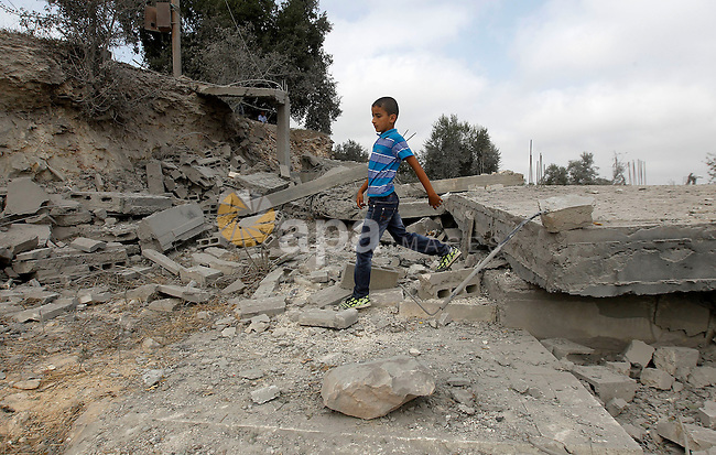 A Palestinian youth inspects the rubble of the home of Mohammed Abed Almajid El-Amaira, a Palestinian accused of involvement in a shooting attack that led to the death of a rabbi, after it was destroyed by Israeli military on August 30, 2016 in the West Bank village of Dura near Hebron. Israel frequently destroys the homes of Palestinians who have carried out attacks. Amaira, a member of the Palestinian Authority security services, was arrested several weeks ago, accused of having helped plan and carry out the attack on July 1, when gunmen opened fire on a car near Hebron. The car crashed, killing rabbi Michael Mark, who led a religious school in the Israeli settlement of Otniel, and wounding two family members, according to the army. Photo by Wisam Hashlamoun