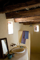 Massive palmwood beams are a striking feature of this bathroom and there is a walk-in shower behind a brick partition