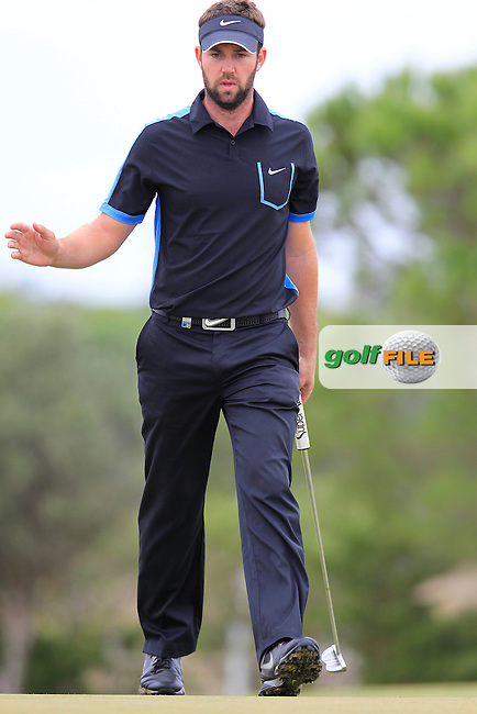 Scott Jamieson (SCO) sinks his birdie putt on the 7th green during Saturday's Round 3 of the 2013 Portugal Masters held at the Oceanico Victoria Golf Club. 12th October 2013.<br /> Picture: Eoin Clarke www.golffile.ie