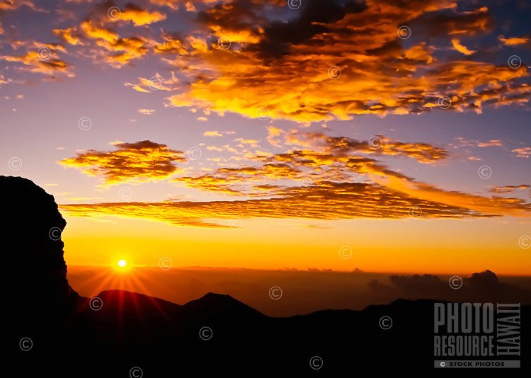 A rare Haleakala National Park sunrise at 9,745 feet in which the overhead clouds still maintained wonderful light and color, Maui.