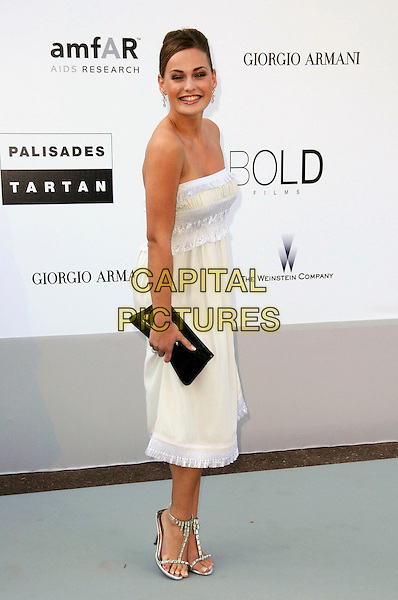 GUEST .arrivals at amfAR's Cinema Against AIDS 2010 benefit gala at the Hotel du Cap, Antibes, Cannes, France during the Cannes Film Festival.20th May 2010.amfar full length white cream pale yellow strapless dress black clutch bag .CAP/CAS.©Bob Cass/Capital Pictures.
