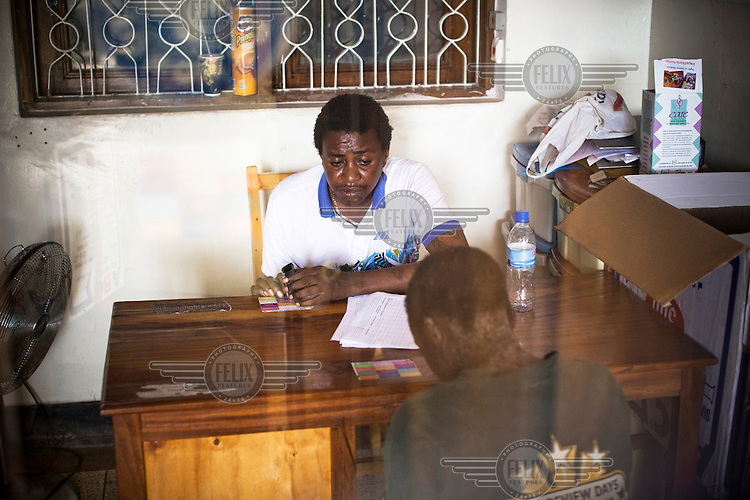 Ramson, a peer educator, talks with a beneficiary who suffers from skin disease at the MDM (Medecins du Monde) drop in centre in Dar Es Salaam. At this centre, drug users can have food, rest, shower and counseling from peer educators and social workers.