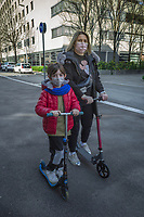 "Switzerland. Canton Ticino. Lugano. A woman and a child wear a mask on their faces to protect themselves from the Coronavirus (also called Covid-19). They are enjoying a short ride outside on a push scooter. Due to the spread of the coronavirus (also called Covid-19), the Federal Council has categorised the situation in the country as ""extraordinary"". It has issued a recommendation to all citizens to stay at home, especially the sick and the elderly. The Federal Council (German: Bundesrat, French: Conseil fédéral, Italian: Consiglio federale, Romansh: Cussegl federal) is the seven-member executive council that constitutes the federal government of the Swiss Confederation. From March 16 the government ramped up its response to the widening pandemic, ordering the closure of bars, restaurants, sports facilities and cultural spaces. Only businesses providing essential goods to the population – such as grocery stores, bakeries and pharmacies – are to remain open. 21.03.2020 © 2020 Didier Ruef"