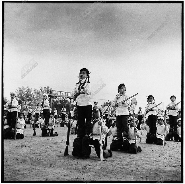 "As part of the national defense against ""imperialism abroad and revisionists at home,"" school-children of the ""Little Red Militia"" and workers from an electrical-component factory participate in militia drills.  Acheng county, 30 May 1965"