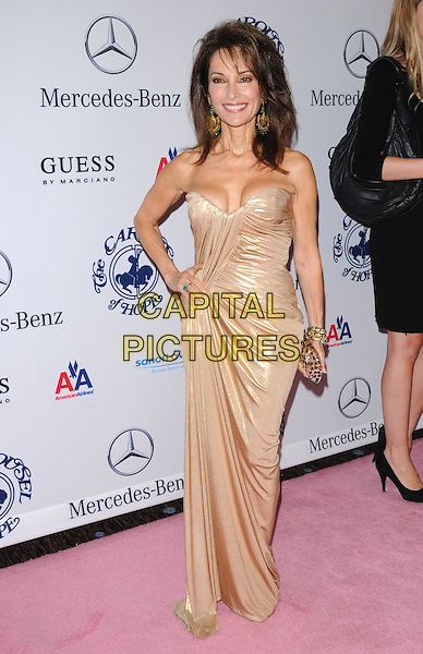 SUSAN LUCCI .at The 32nd Annual Carousel of Hope Ball held at The Beverly Hilton hotel in Beverly Hills, California, USA, .October 23rd 2010..full length strapless gold shiny dress hand on hip lame cleavage clutch bag                                    .CAP/RKE/DVS.©DVS/RockinExposures/Capital Pictures.