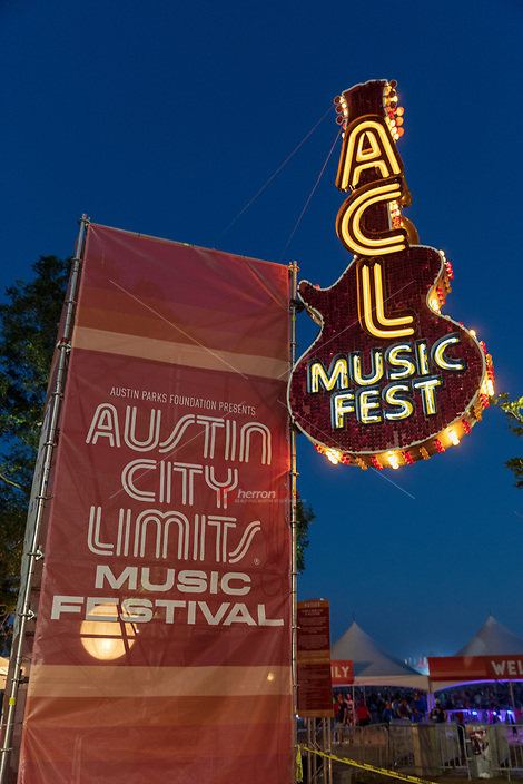 A neon Austin City Limits Music Festival sign lights the nightime sky at Zilker Park as thousands of concert goes enjoy all genres from over 100 live bands.
