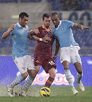 Calcio, Serie A: Lazio vs Roma. Roma, stadio Olimpico, 11 novembre 2012..AS Roma midfielder Miralem Pjanic, of Bosnia, center, fights for the ball agaisnt Lazio defenders Andre Dias, of Brazil, left, and  Abdoulay Konko, of France, during the Italian Serie A football match between Lazio and AS Roma, at Rome's Olympic stadium, 11 November 2012..UPDATE IMAGES PRESS/Riccardo De Luca