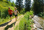 A young couple runs along a trail in the Cache Creek area near Jackson, Wyoming.