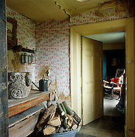 Layers of wallpaper peel off the walls in a room which is used to store firewood and unused furniture