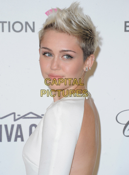 Miley Cyrus.The 21st Annual Elton John AIDS Foundation Academy Awards Viewing Party held at The City of West Hollywood Park in West Hollywood, California, USA..February 24th, 2013.oscars headshot portrait white chains straps backless side spiked platinum quiff dark buzzed roots hair dyed blonde earrings .CAP/DVS.©DVS/Capital Pictures.