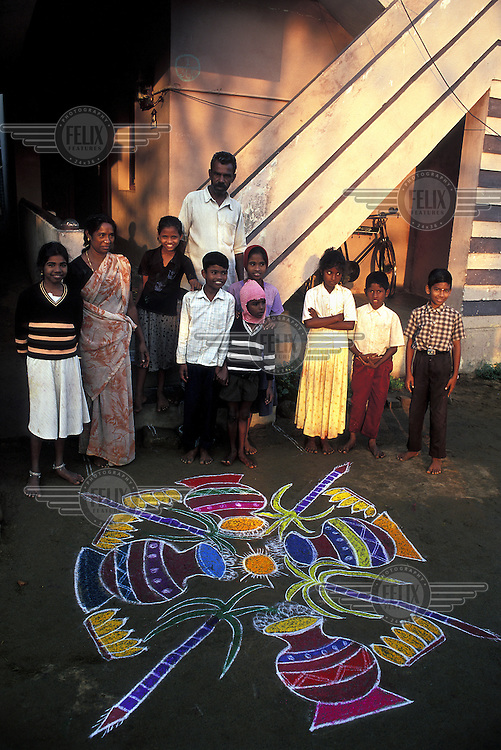 At start of the Pongal Harvest Festival a a family stand next to the Kolam design that the female members of the household have painted in front of their home using a paste made of newly harvested rice.