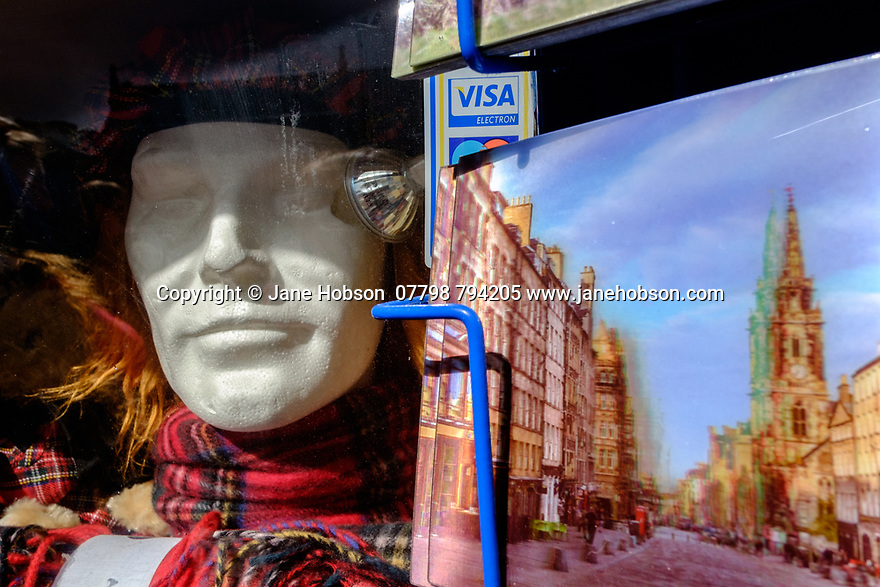 """Edinburgh, UK. 15.04.2017. Close-up of shop window, with polystyrene head sporting a """"Jimmy"""" hat, and some postcards. Photograph © Jane Hobson."""