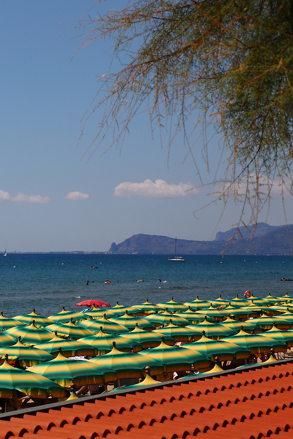 Sperlonga: A view of the beach towards North, with coloured beach umbrella in foreground. On the background, the nearest head along the coast, that closes the gulf, is the cliff of Pisco Montano, behind which is Monte Sant&rsquo;Angelo, where is located Terracina. This is an enlargement of a part of the original photo.<br />