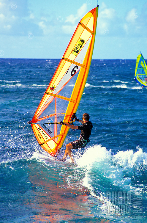 A windsurfer heads out at  Hookipa Beach Park on Maui's North Shore. This is Maui's most popular surf and windsurfing beach just off the Hana Highway and near Mama's Fishhouse just outside the town of Paia.