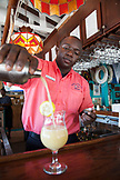 EXUMA, Bahamas. A bartender mixing a drink at the Staniel Cay Yacht Club in Staniel Cay.