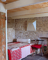 The cosy spare bedroom has exposed stone walls, a slate tiled floor and a traditional red patchwork quilt