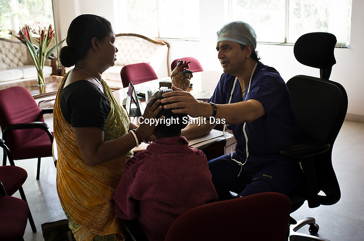 Dr. Devi Prasad Shetty consoles a poor woman who begs him to save her daughters' (right) life during an OPD in his office at the Narayana Hrudayalaya in Bangalore, Karnataka, India. Photo: Sanjit Das/Panos