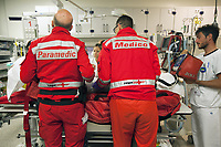 "Switzerland. Canton Ticino. Lugano. Ospedale Civico. Emergency room. The Rega has rescued an elderly man lying on a stretcher and suffering from a heart problem. Medical care. The paramedic Paolo Menghetti (L) and the emergency physician Michele Musiari give all needful medical informations to the hospital's medical team. All Rega helicopters carry a crew of three: a pilot, an emergency physician, and a paramedic who is also trained to assist the pilot for radio communication, navigation, terrain/object avoidance, and winch operations. The name Rega was created by combining letters from the name ""Swiss Air Rescue Guard"" as it was written in German (Schweizerische Rettungsflugwacht), French (Garde Aérienne Suisse de Sauvetage), and Italian (Guardia Aerea Svizzera di Soccorso). Rega is a private, non-profit air rescue service that provides emergency medical assistance in Switzerland. Rega mainly assists with mountain rescues, though it will also operate in other terrains when needed, most notably during life-threatening emergencies. 10.09.2017 © 2017 Didier Ruef"