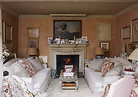 A pair of matching sofas covered in oyster-coloured silk have been arranged on either side of a cosy faux-fur rug in front of the marble fireplace